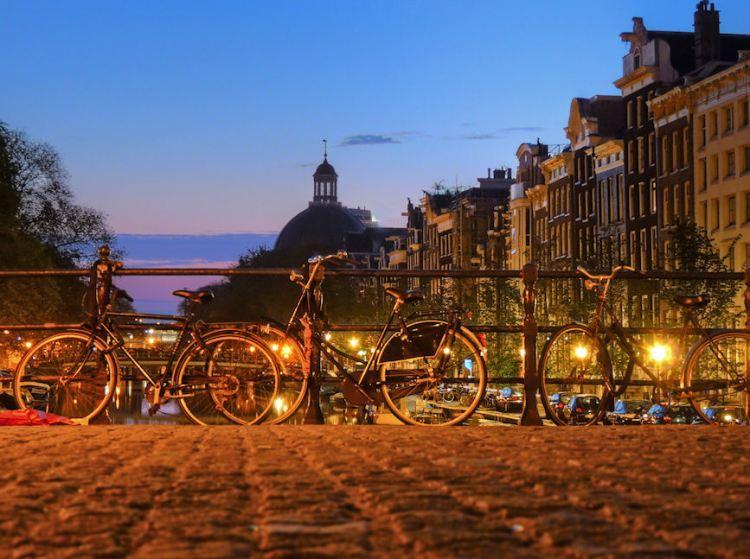 Three bikes on the canal bridge in Amsterdam, by joiseyshowaa via Flickr